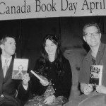 A black and white photo of three people holding books in front of a banner that says Canada Book Day Awards