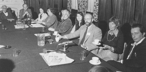 A black and white photo of people sitting at a desk