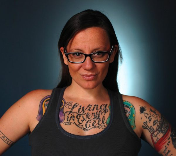 """Cherie Dimaline wears a tanktop that shows her tattoos including one that reads """"Living in Every Cell"""" as she looks directly into the camera with a  light behind her"""