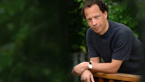 Lawrence Hill leans over a wooden railing with tree leaves in the background. He is wearing a dark grey tshirt.