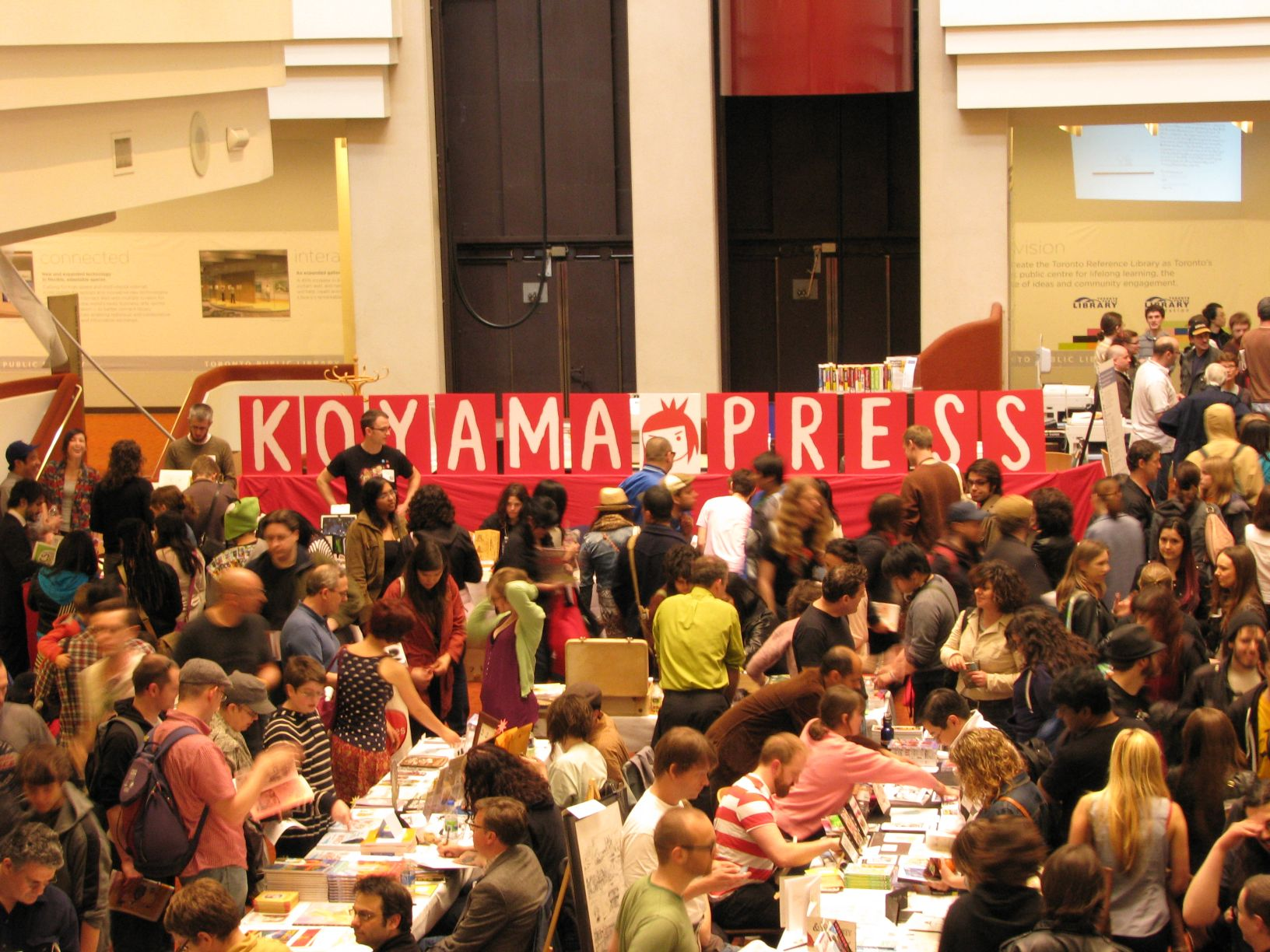 Photo of a crowd in front of a sign that says Koyama Press