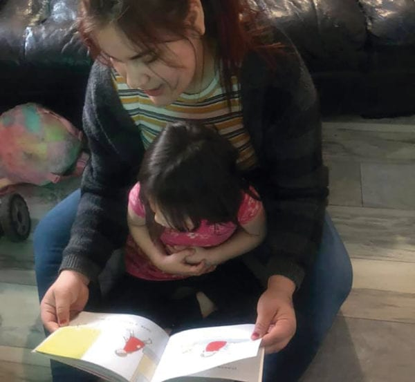 A photo of a woman reading a book with a young girl