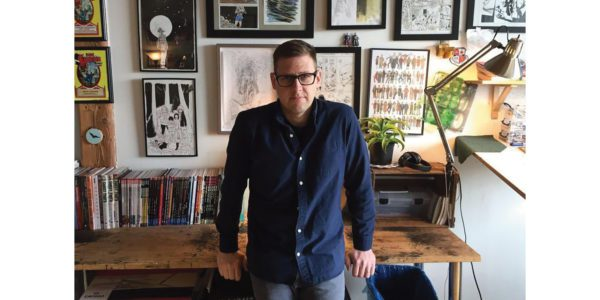 A photo of author Jeff Lemire leaning against the desk in his office